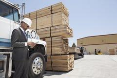 使用片剂个人计算机的非裔美国人的公承包商,当支持采伐的卡车时 免版税库存图片