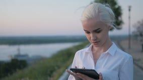 使用片剂个人计算机的年轻美丽的女商人户外在日落 免版税图库摄影