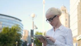 使用片剂个人计算机的年轻美丽的女商人画象户外 图库摄影