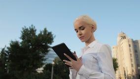 使用片剂个人计算机的年轻美丽的女商人画象户外 免版税库存照片