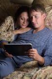 使用片剂个人计算机,愉快的夫妇一起 免版税库存照片