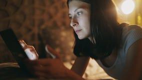使用片剂互联网瘾和失眠的计算机becuause少妇在家说谎在床上在夜间 免版税库存照片