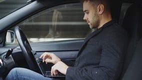 使用片剂便携式计算机的可爱的年轻人,当坐在他的汽车里面户外时 库存图片