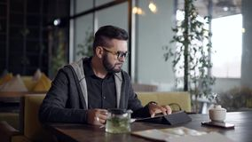 使用片剂和啜饮的热的饮料茶从杯子,单独年轻人在咖啡馆单独休息自白天, 股票视频