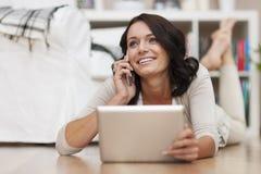 使用片剂和电话的妇女 免版税库存照片