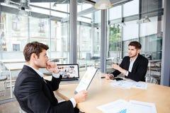 使用片剂和膝上型计算机的两个年轻商人在业务会议 库存图片