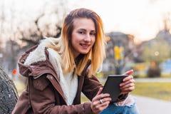 使用片剂室外微笑的少妇 免版税图库摄影