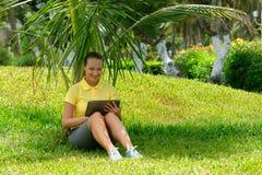 使用片剂室外放置在草的少妇,微笑 库存照片