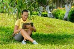 使用片剂室外放置在草的少妇,微笑 免版税库存图片
