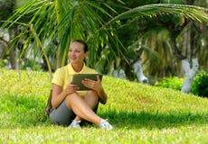 使用片剂室外放置在草的少妇,微笑 图库摄影