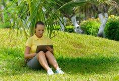 使用片剂室外放置在草的少妇 免版税图库摄影