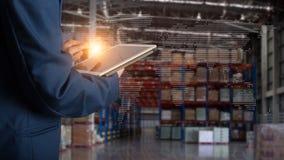 使用片剂检查和控制的商人经理为有现代商业仓库后勤学的工作者 免版税库存照片