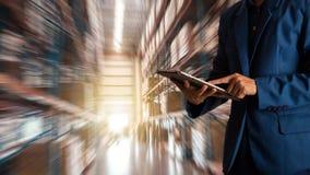 使用片剂检查和控制的商人经理为有现代商业仓库的工作者 库存图片