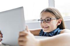 使用片剂的一个逗人喜爱的孩子在学校 免版税库存照片