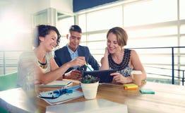 使用片剂的三个成功的商人的图象在会议上期间 免版税图库摄影