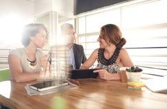 使用片剂的三个成功的商人的图象在会议上期间 图库摄影