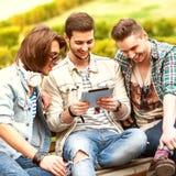 使用片剂的三个年轻人朋友 免版税库存图片
