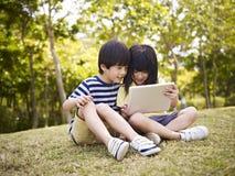 使用片剂的两个亚裔孩子户外 免版税库存照片