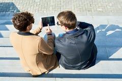 使用片剂的两个人户外 免版税库存图片