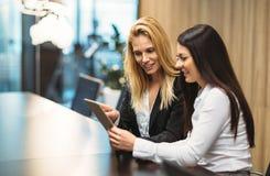 使用片剂的两名可爱的女实业家画象在办公室 免版税库存照片