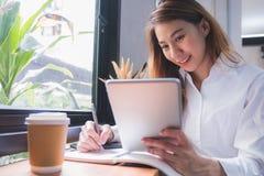 使用片剂的亚洲偶然妇女自由职业者和写计划和s 免版税图库摄影