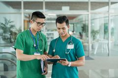 使用片剂的亚裔医生在医院 图库摄影