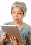 使用片剂的亚裔老人 库存照片