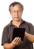 使用片剂的亚裔老人 免版税库存图片