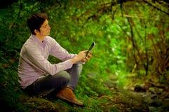 使用片剂的人在森林 免版税库存照片