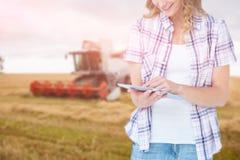 使用片剂的俏丽的行家的综合图象反对农业场面 免版税库存照片