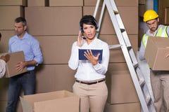 使用片剂的俏丽的仓库经理在忙碌期间 免版税库存图片