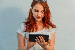 使用片剂的典雅的姜头发年轻女实业家或学生倾斜对白色墙壁,看屏幕 免版税库存图片