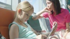 使用片剂的可爱的女孩在机场,当等待他们的飞行时 旅行海外与孩子 影视素材