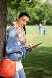 使用片剂的可爱的妇女在公园微笑 免版税库存照片