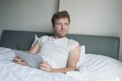 使用片剂的可爱的白种人年轻人在床早晨 库存图片