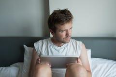 使用片剂的可爱的白种人年轻人在床早晨 免版税库存照片