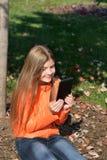 使用片剂的女孩在公园 免版税库存图片