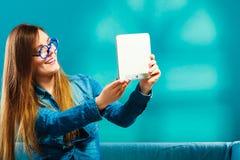 使用片剂的女孩采取图片的她自己蓝色颜色 免版税库存图片