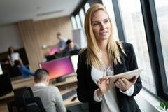 使用片剂的女实业家在信息技术办公室 库存图片