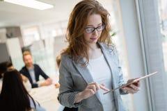 使用片剂的女实业家在信息技术办公室 免版税库存图片