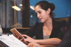 使用片剂的女实业家在她的工作场所 免版税库存图片