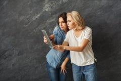使用片剂的好奇女性朋友在黑暗的演播室背景 免版税图库摄影