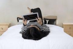 使用片剂的妇女在卧室 免版税库存照片