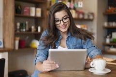 使用片剂的妇女在咖啡馆 免版税库存图片
