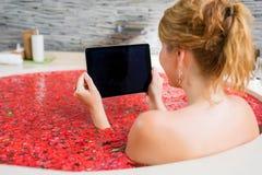 使用片剂的妇女在花浴 图库摄影