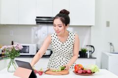 使用片剂的妇女,当做健康沙拉在厨房时 免版税库存照片