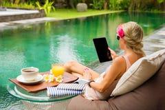 使用片剂的妇女,当放松由异乎寻常的热带水池时 免版税库存照片