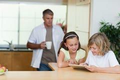 使用片剂的孩子在有父亲的厨房在他们之后 库存照片