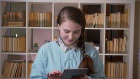 使用片剂的年轻俏丽的女生特写镜头画象看照相机在大学图书馆户内 股票视频