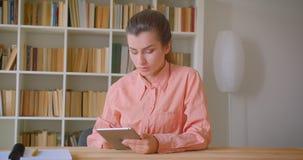 使用片剂的年轻可爱的女生特写镜头画象在大学图书馆 股票视频